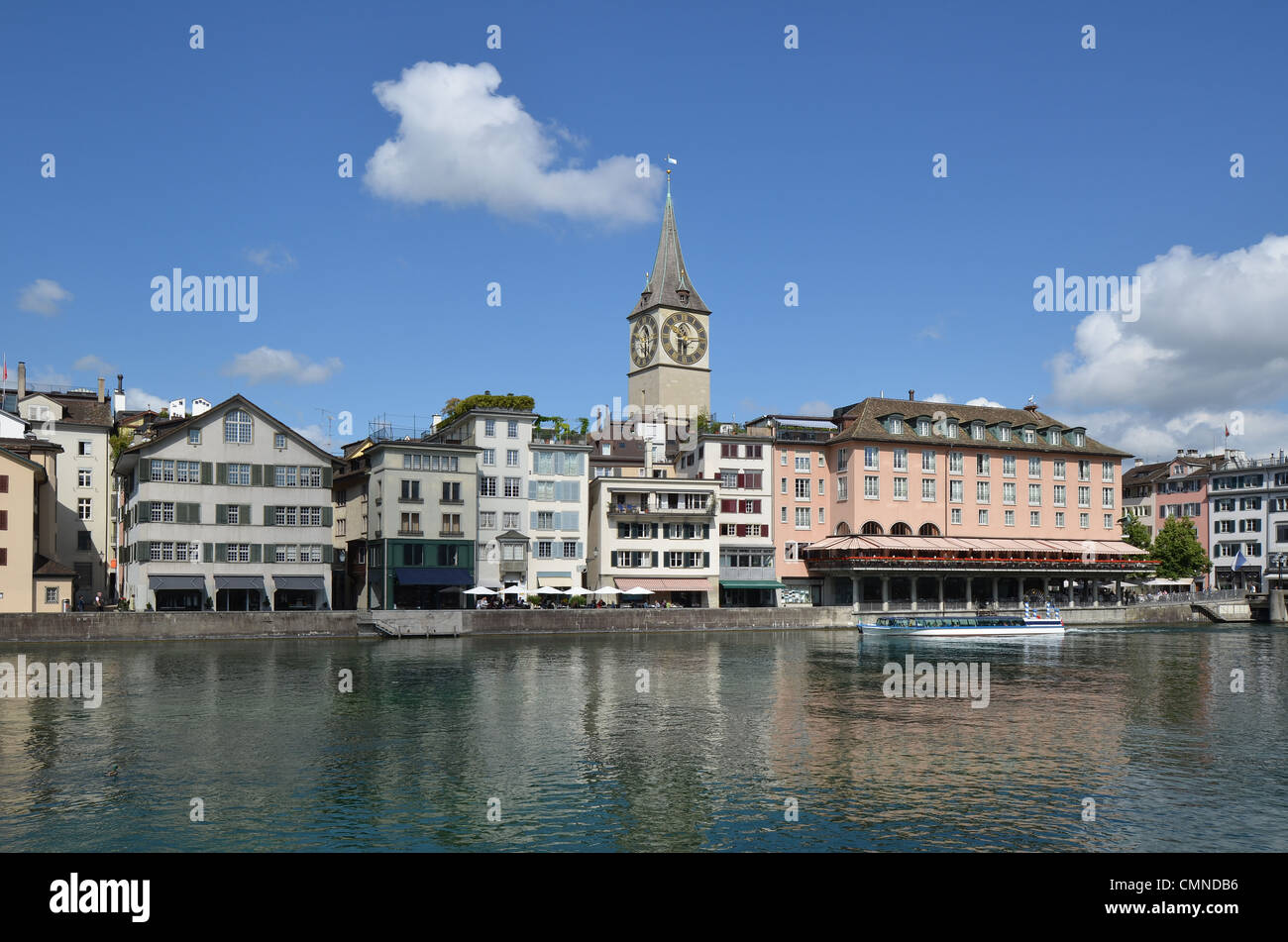 The River Limmat waterfront of Zurich with the spire of St. Peters church. - Stock Image