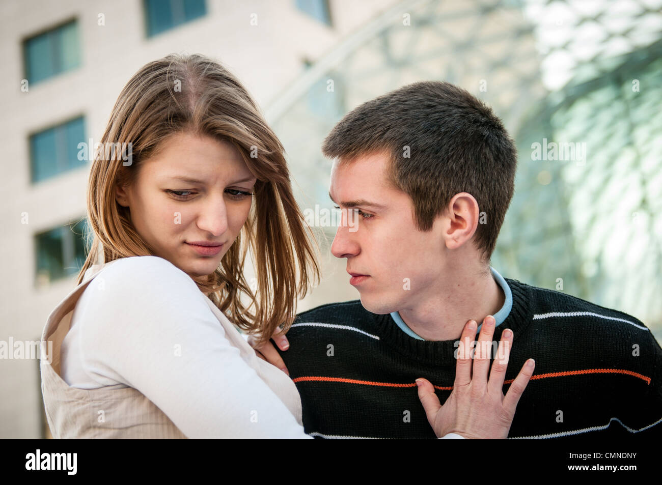 Lifestyle image of young woman refusing man outside on street having relationship problems - Stock Image