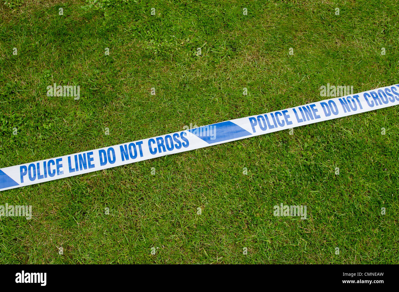 White tape with 'Police Line Do Not Cross' printed on it laying on the grass. - Stock Image