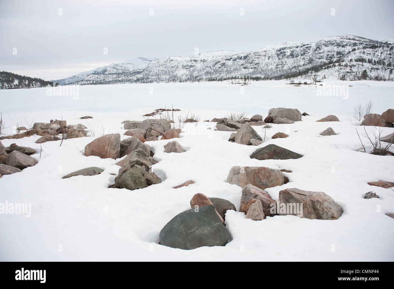 Snow-covered granite rocks at the banks of Breivevatnet, a lake near Hovden and Breive in Aust-Agder, South Norway - Stock Image