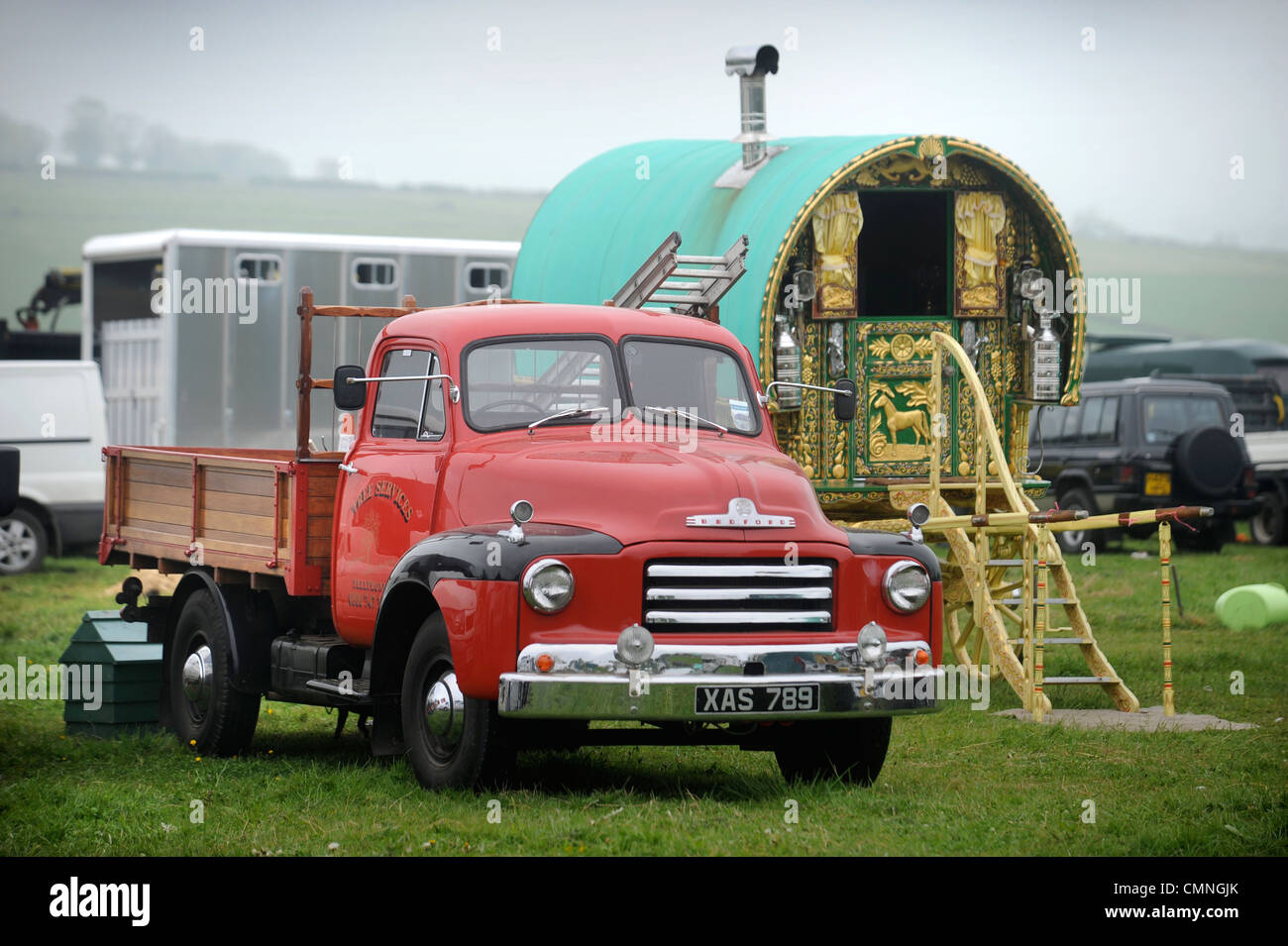 A classic truck and a decorative horse drawn caravan or Gypsy wagon at the Stow-on-the-Wold horse fair May 2009 - Stock Image