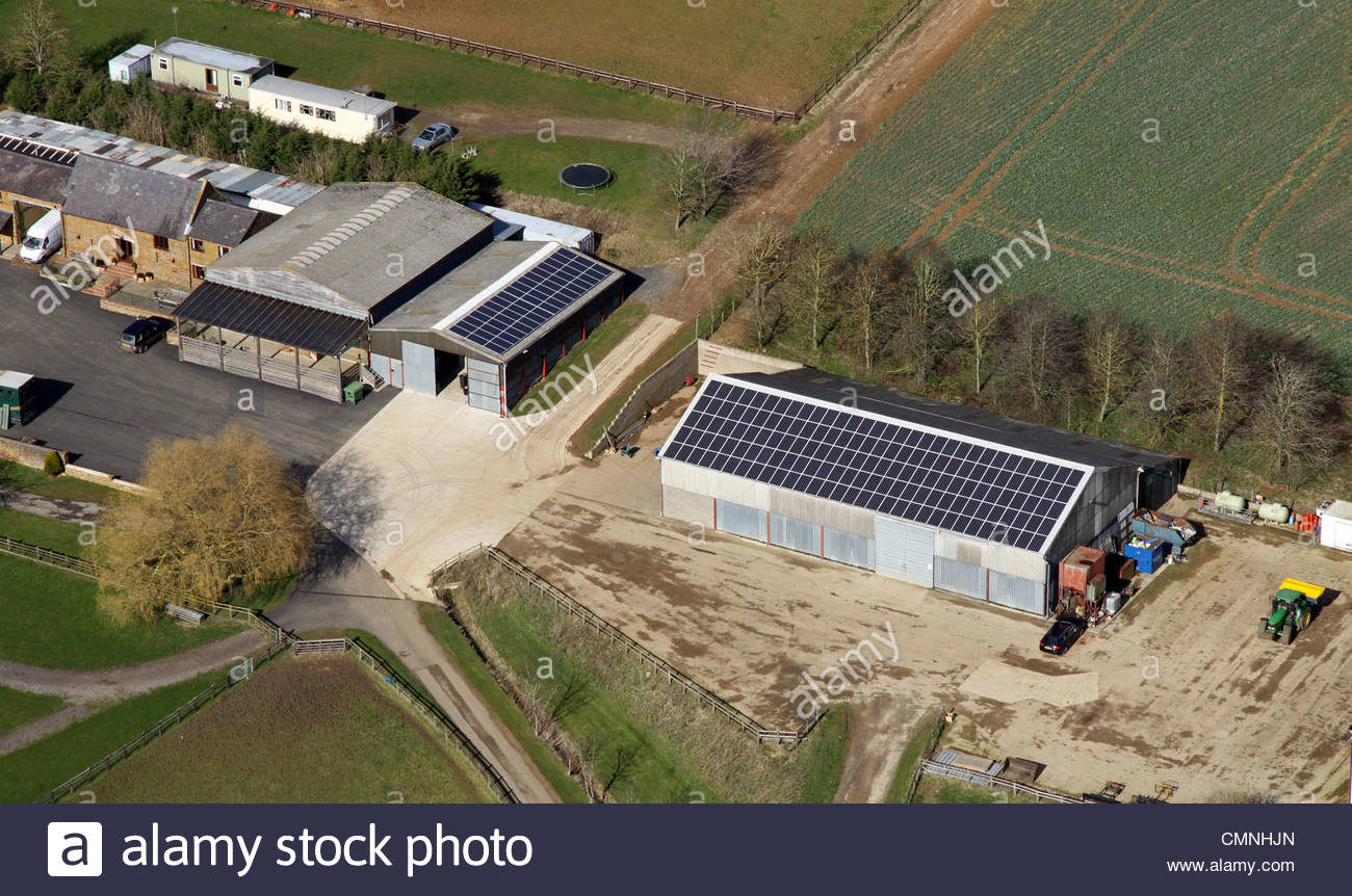 aerial view of a farm with solar panels on two barn buildings - Stock Image