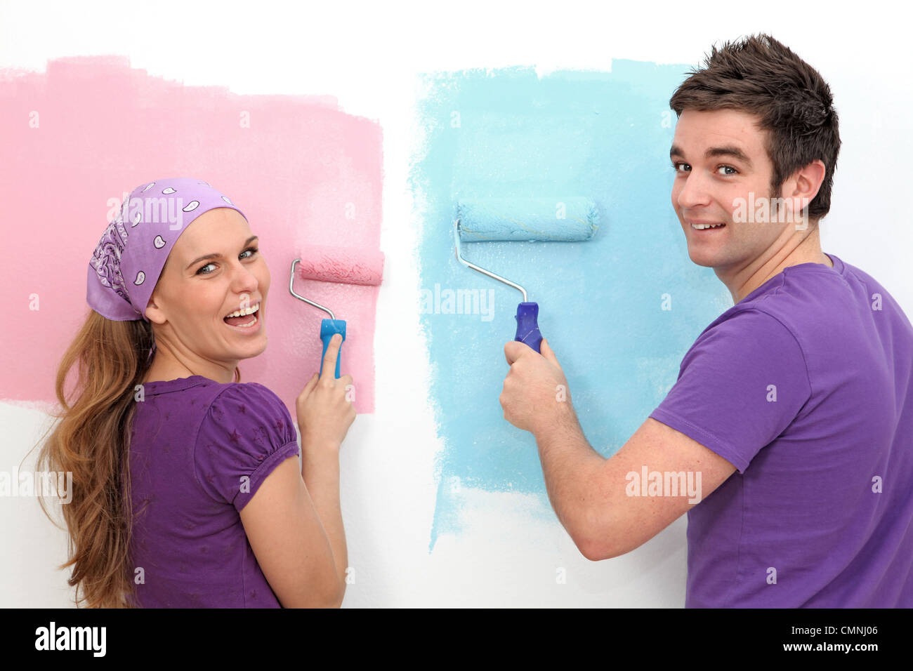 happy couple painting first home - Stock Image