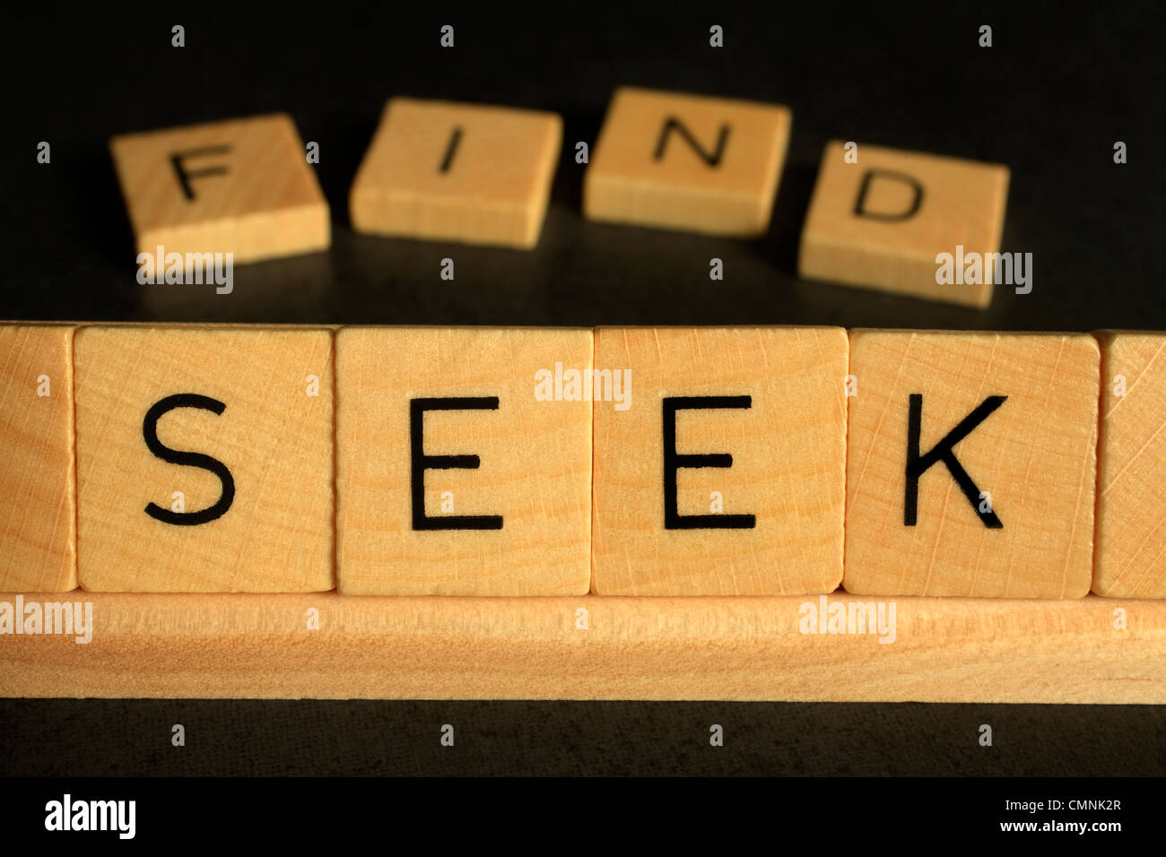 The words Seek and Find spelled out in scrabble, concepts of searching, spirituality, lost and found. - Stock Image