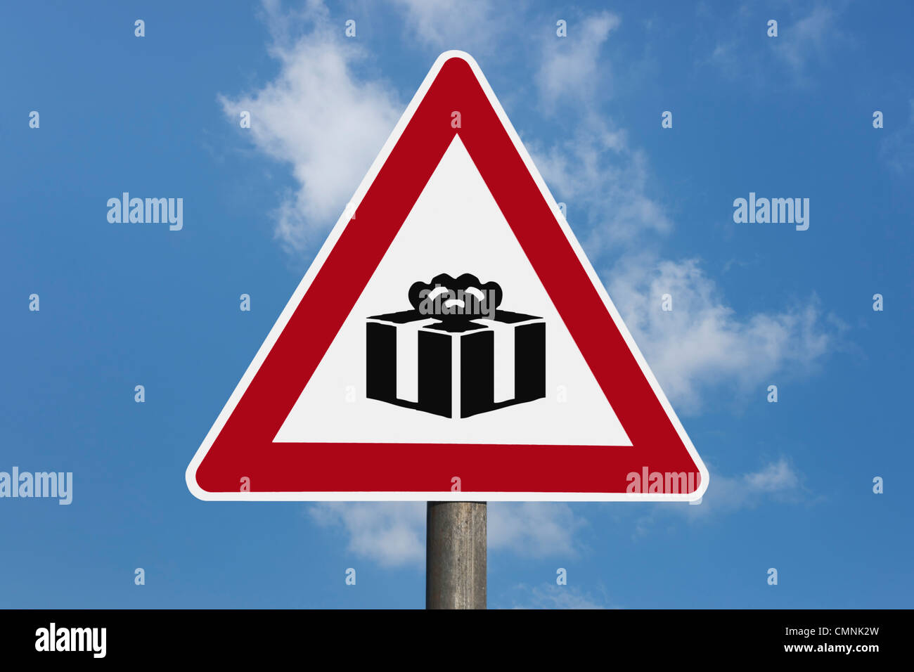Detail photo of a danger sign with a present in the middle, background sky. - Stock Image