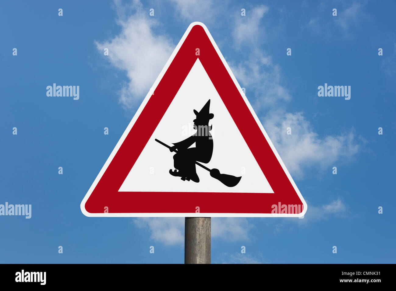 Detail photo of a danger sign with a witch on a broom in the middle, background sky. Stock Photo