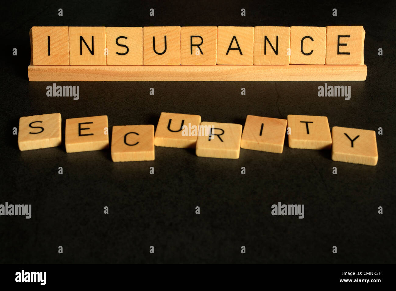 Insurance and security cpncept, with words spelled out in alphabet letters. On a dark, textured background. - Stock Image