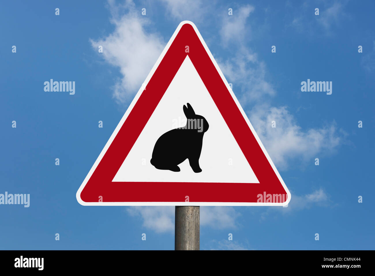 Detail photo of a danger sign with a bunny in the middle, background sky. - Stock Image