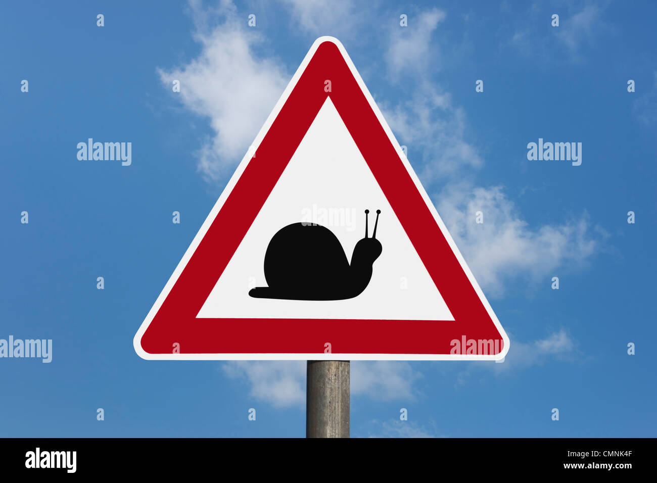 Detail photo of a danger sign with a snail in the middle, background sky. - Stock Image
