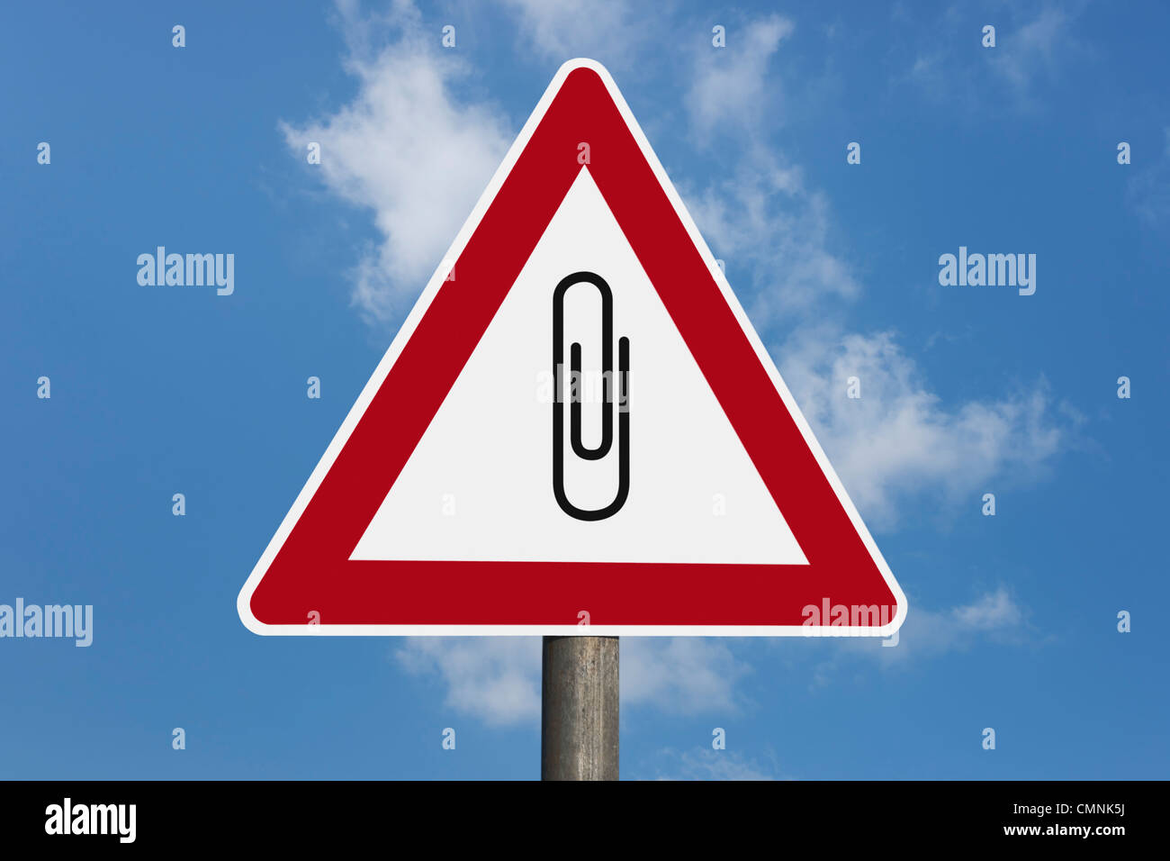 Detail photo of a danger sign with a paper clip in the middle, background sky. Stock Photo