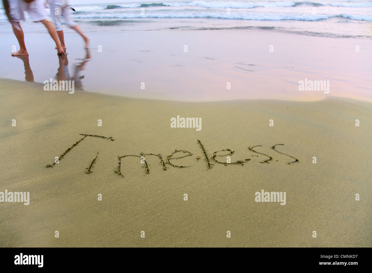 Handwriting word Timeless written on the sand - Stock Image