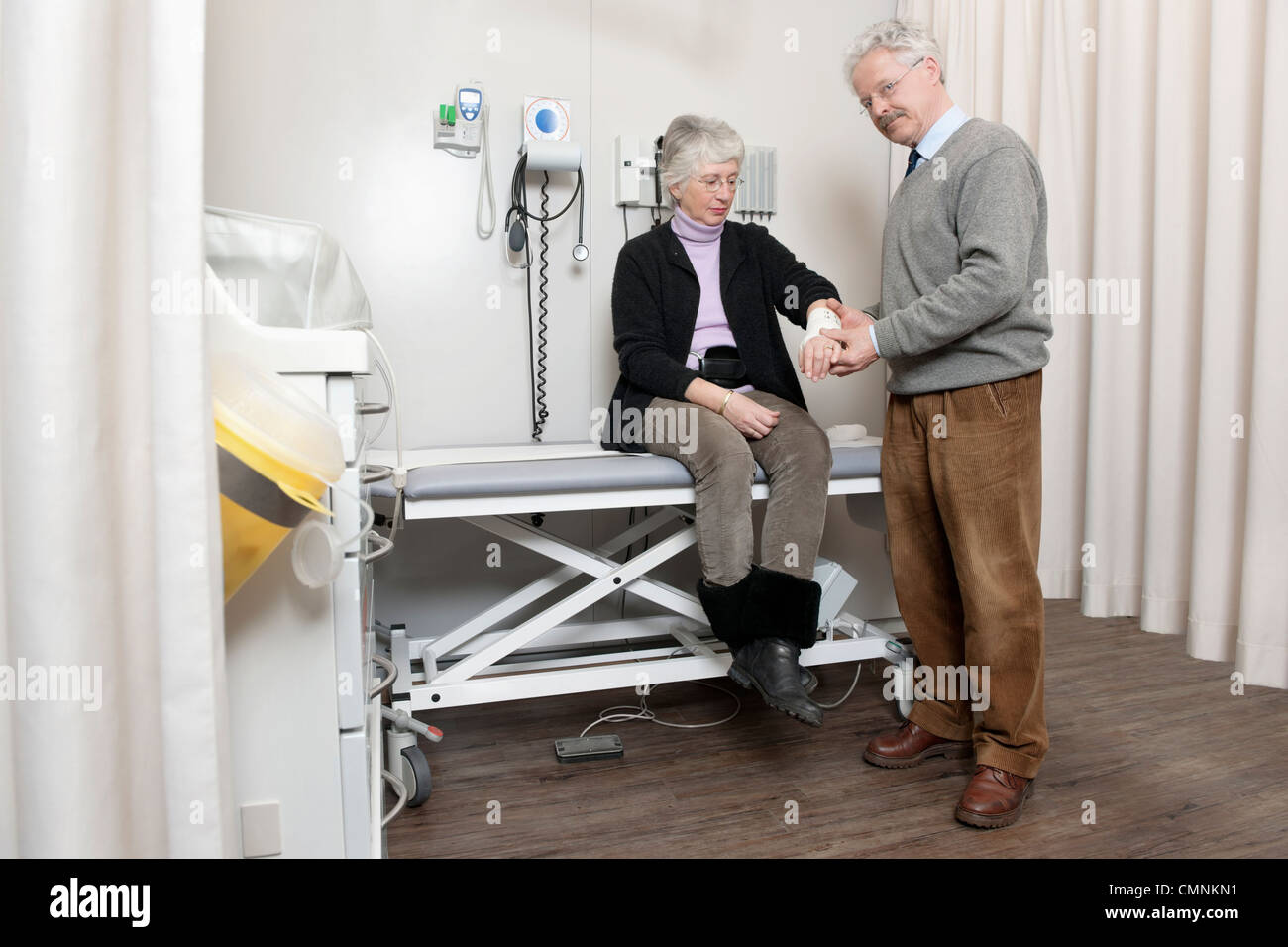 General Practitioner posing in his practice, whilst examining the bandaged sprained wrist of a middle aged woman - Stock Image