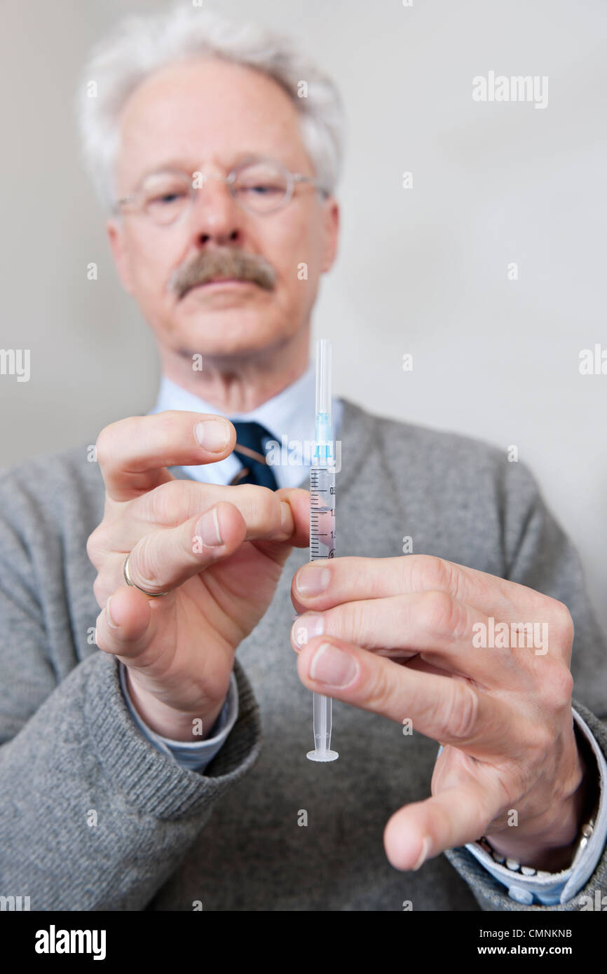 Doctor flicking the air bubbles from a syringe, filled with a drug - Stock Image