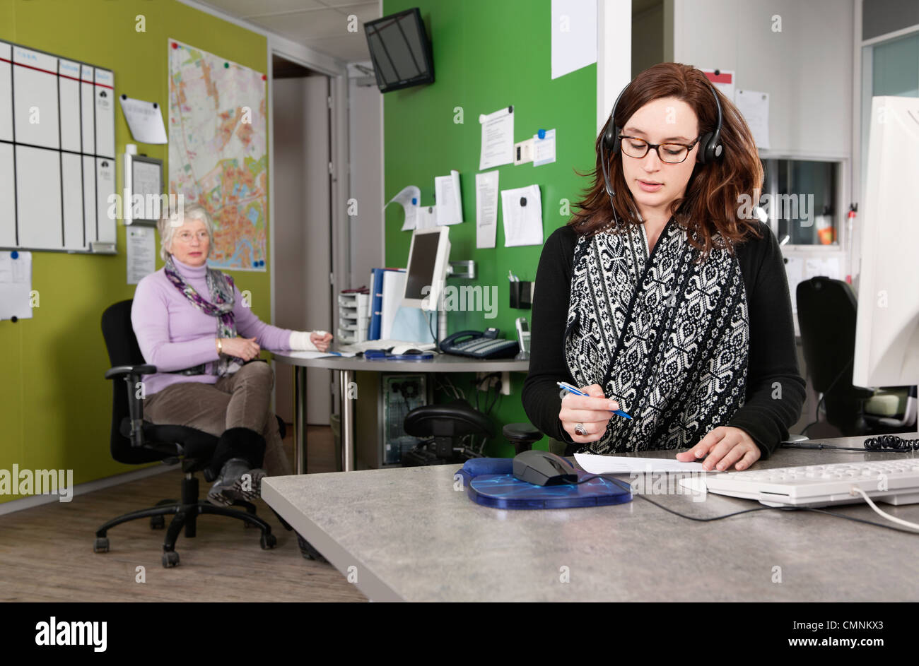 Two employees at work in an emergency response center of a hospital, taking calls from patients. - Stock Image