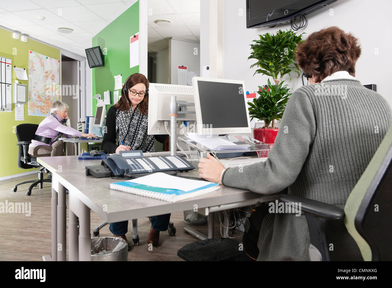 Returners working at the emergency call center of a hospital, answering phone calls from patients, making appointments, - Stock Image