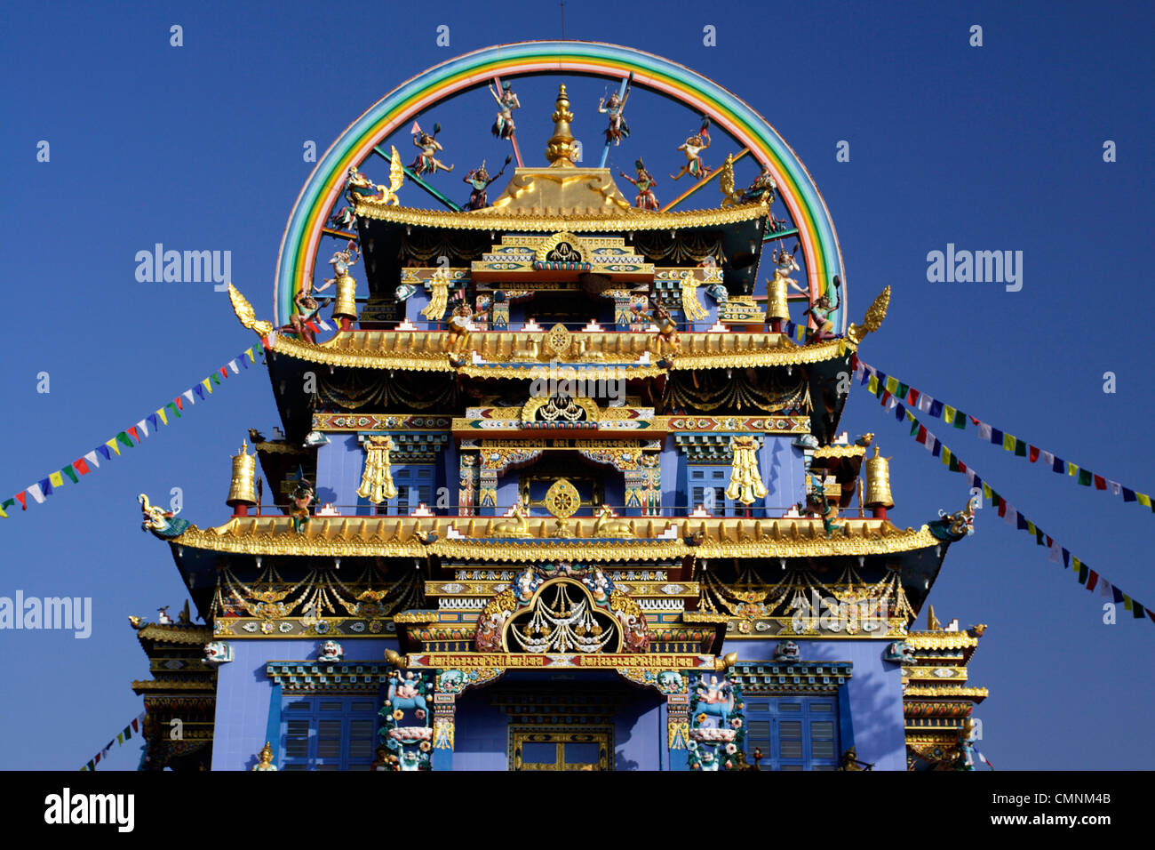 The wheel of life tops the roof of the Golden Buddha Temple, a Tibetan Buddhist monastery at Namdroling, Karnataka, - Stock Image