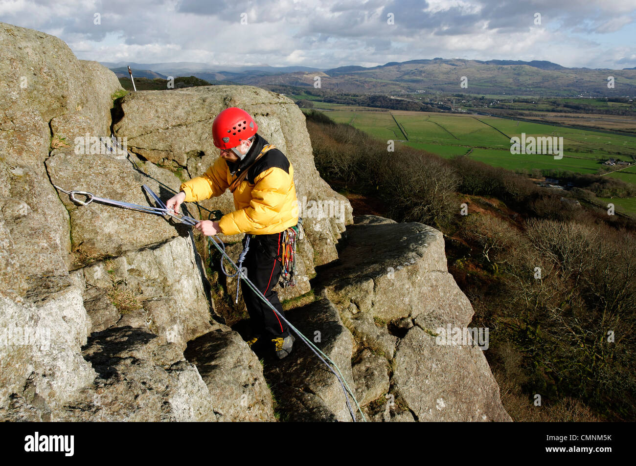 A rock climber building a belay at the Upper Tier of Tremadog North Wales - Stock Image