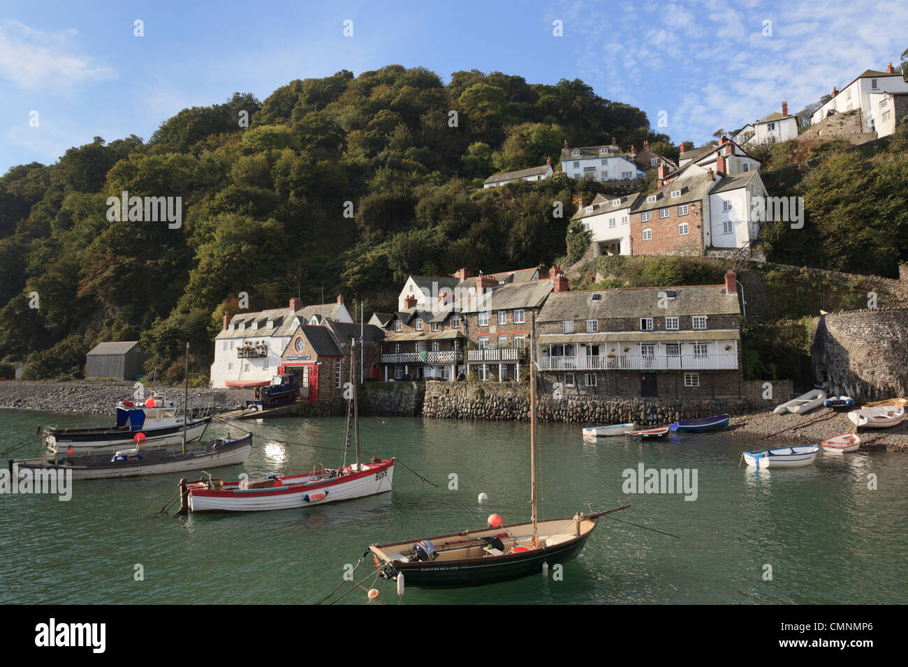 Clovelly, North Devon, England, UK. Coastal scene with boats in the harbour below the village on a steep hillside - Stock Image
