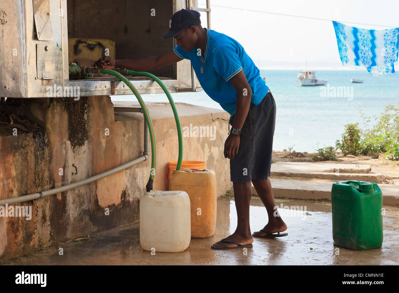 Local man with containers for collecting desalinated fresh drinking water from a bowser. Sal Rei, Boa Vista, Cape - Stock Image