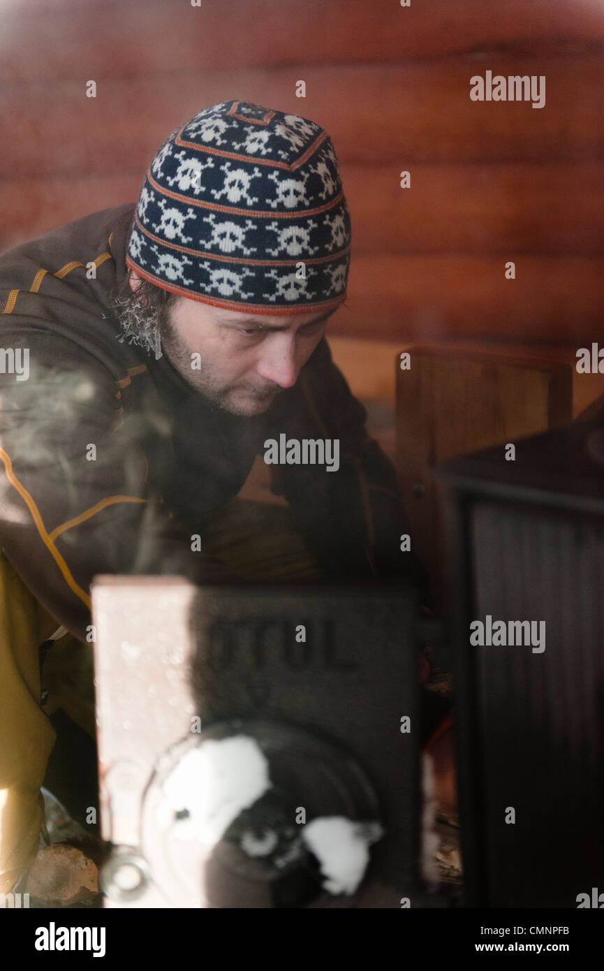 A man initiating fire inside a hut in Kittilä, Finnish Lapland. - Stock Image