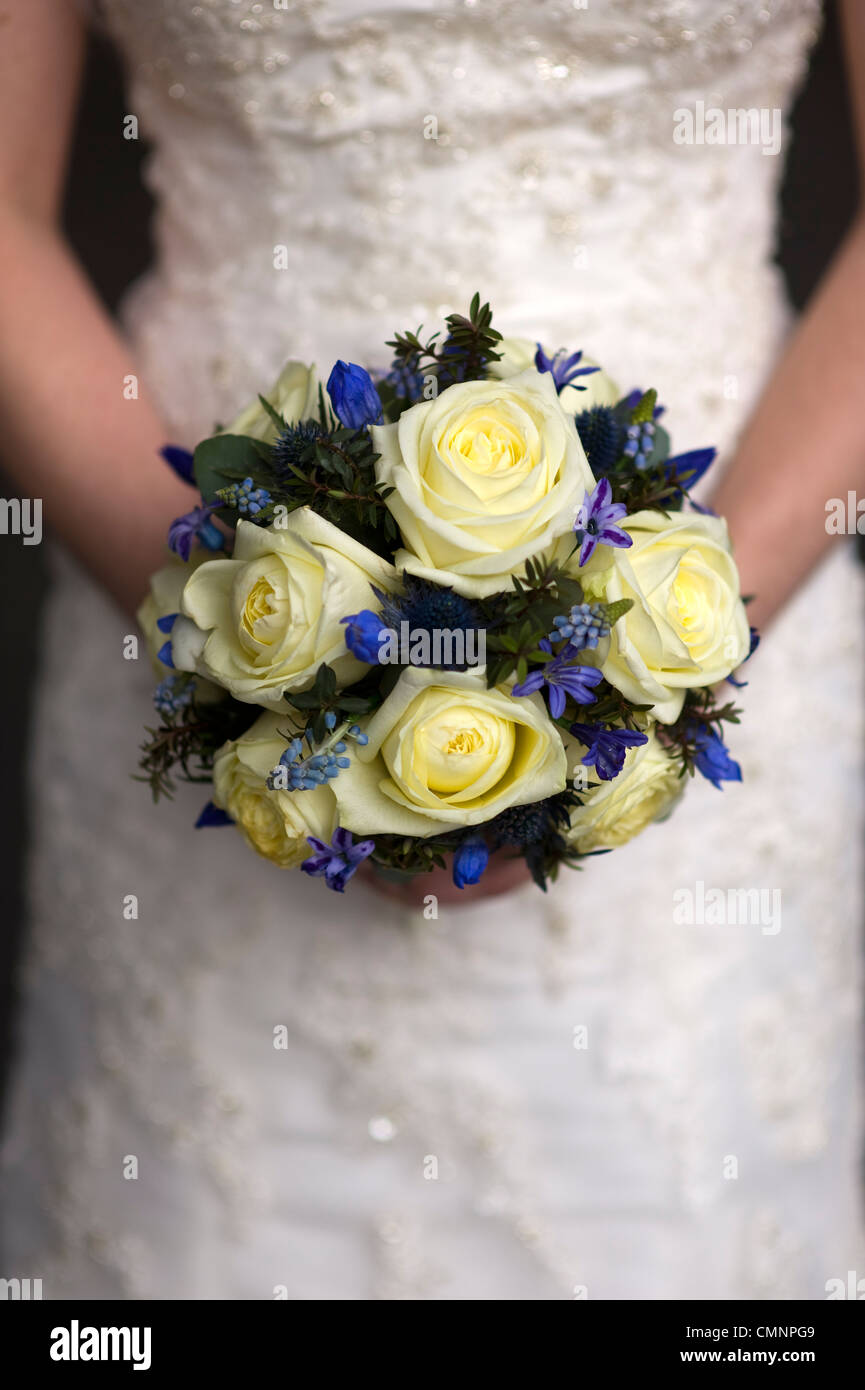 wedding bouquet of cream roses and spring flowers held by a bride Stock Photo