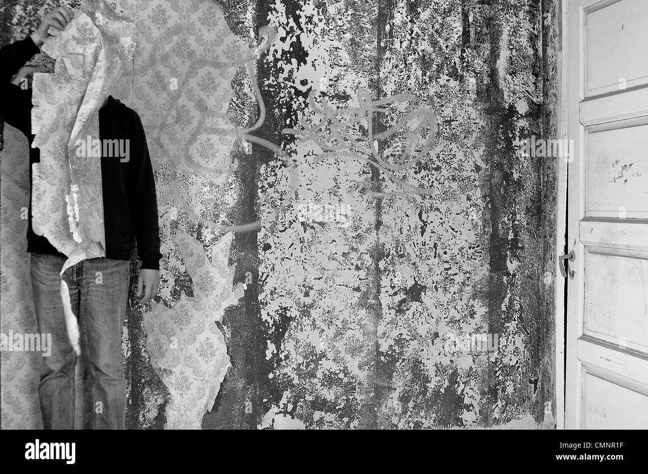 Figure obscured with torn wallpaper in abandoned interior. Black and white. - Stock Image