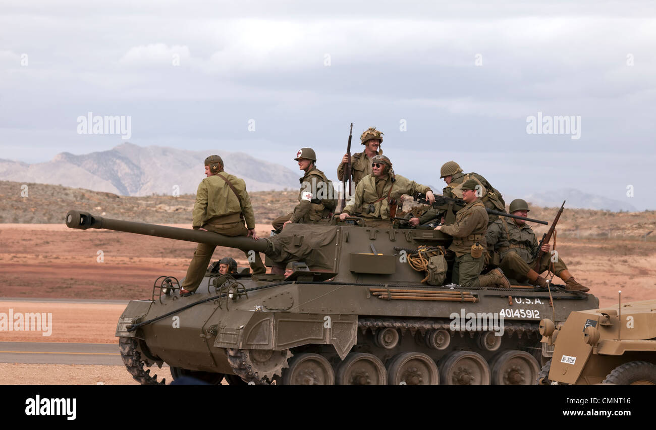 Army troops riding on top of vintage antique World War II US tank during a display in desert setting. Stock Photo