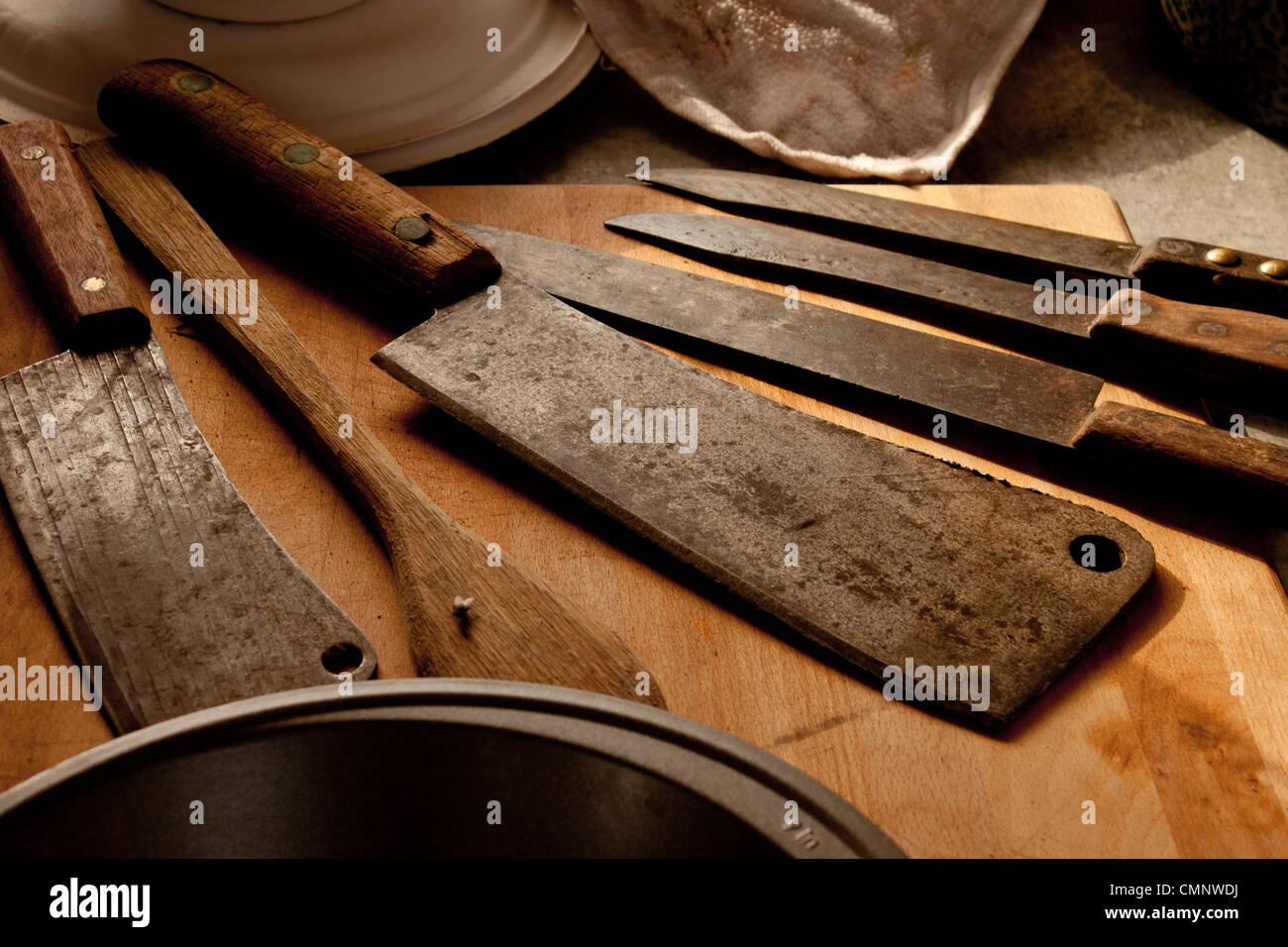 Antique butcher cleaver knifes on cutting board. - Stock Image