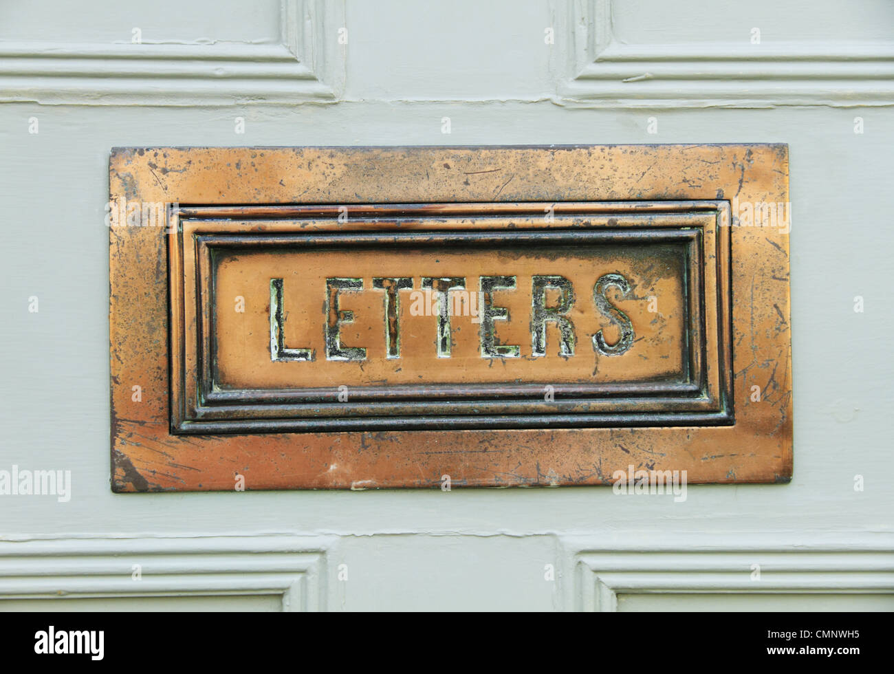 An old antique ornate brass letter mail box on a front door in Lewes, East Sussex, England. - Stock Image