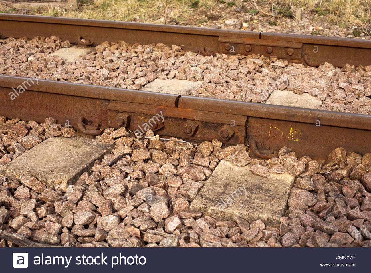 Side view of railway track showing ballast, sleepers and fishplate joint bar - Stock Image