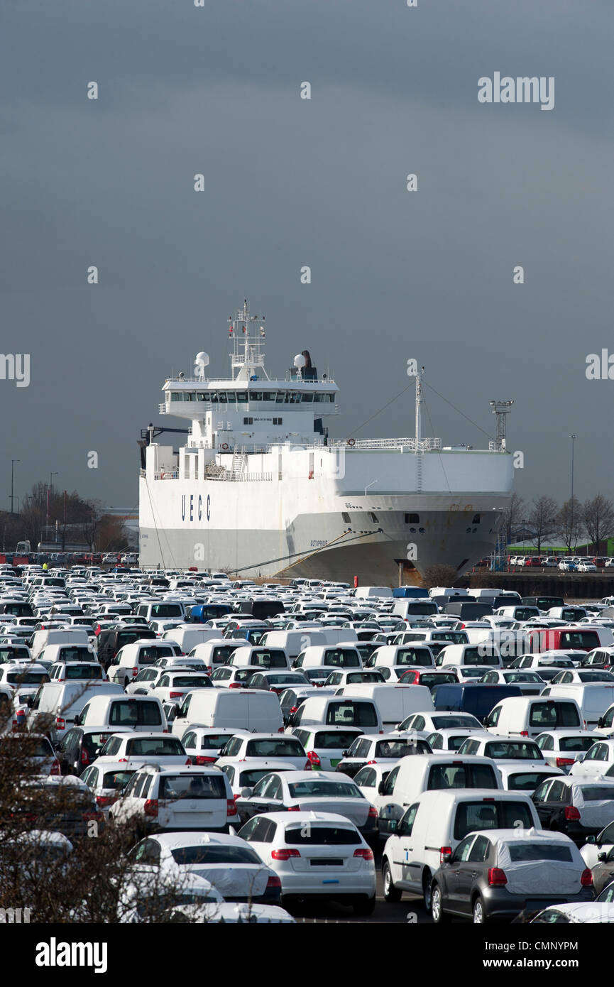 Cars at Grimsby Docks which have been either been imported or exported by the ship in the background. - Stock Image