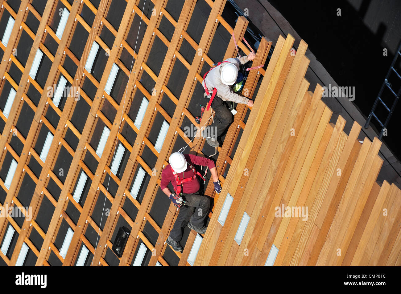 Construction workers / steeplejacks / roofers protected by safety harnesses, hard hats and ropes attaching wooden - Stock Image