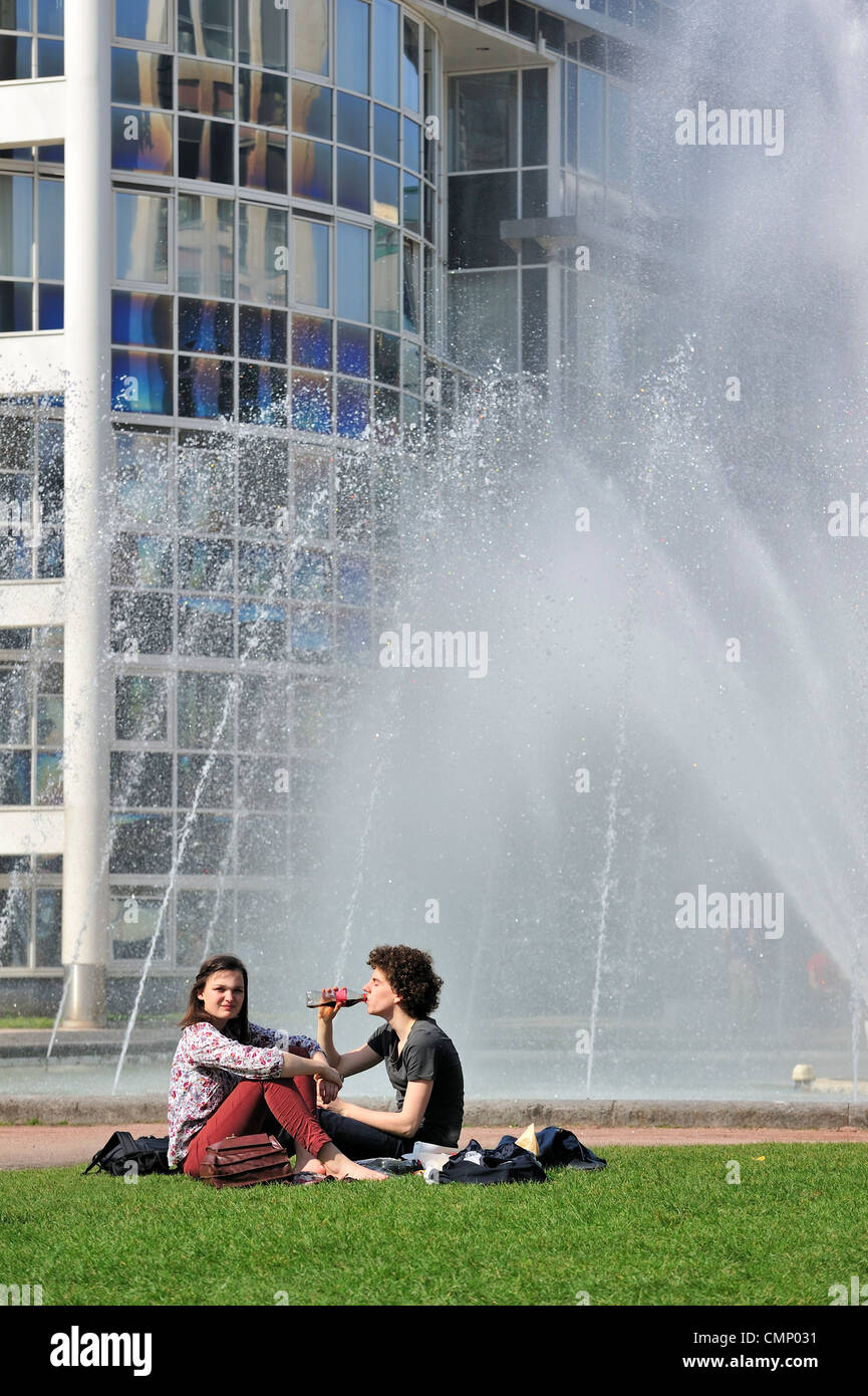 Couple of youngsters enjoying the first spring sun on a hot day in city park with fountain at Ghent, Belgium - Stock Image