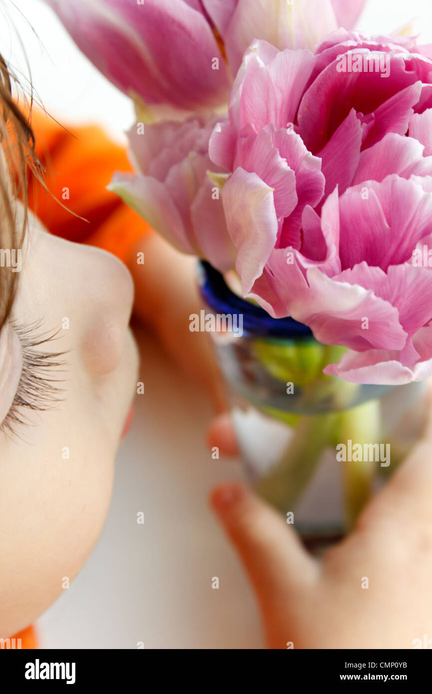 Little girl smelling the scent of  two purple flowers. - Stock Image
