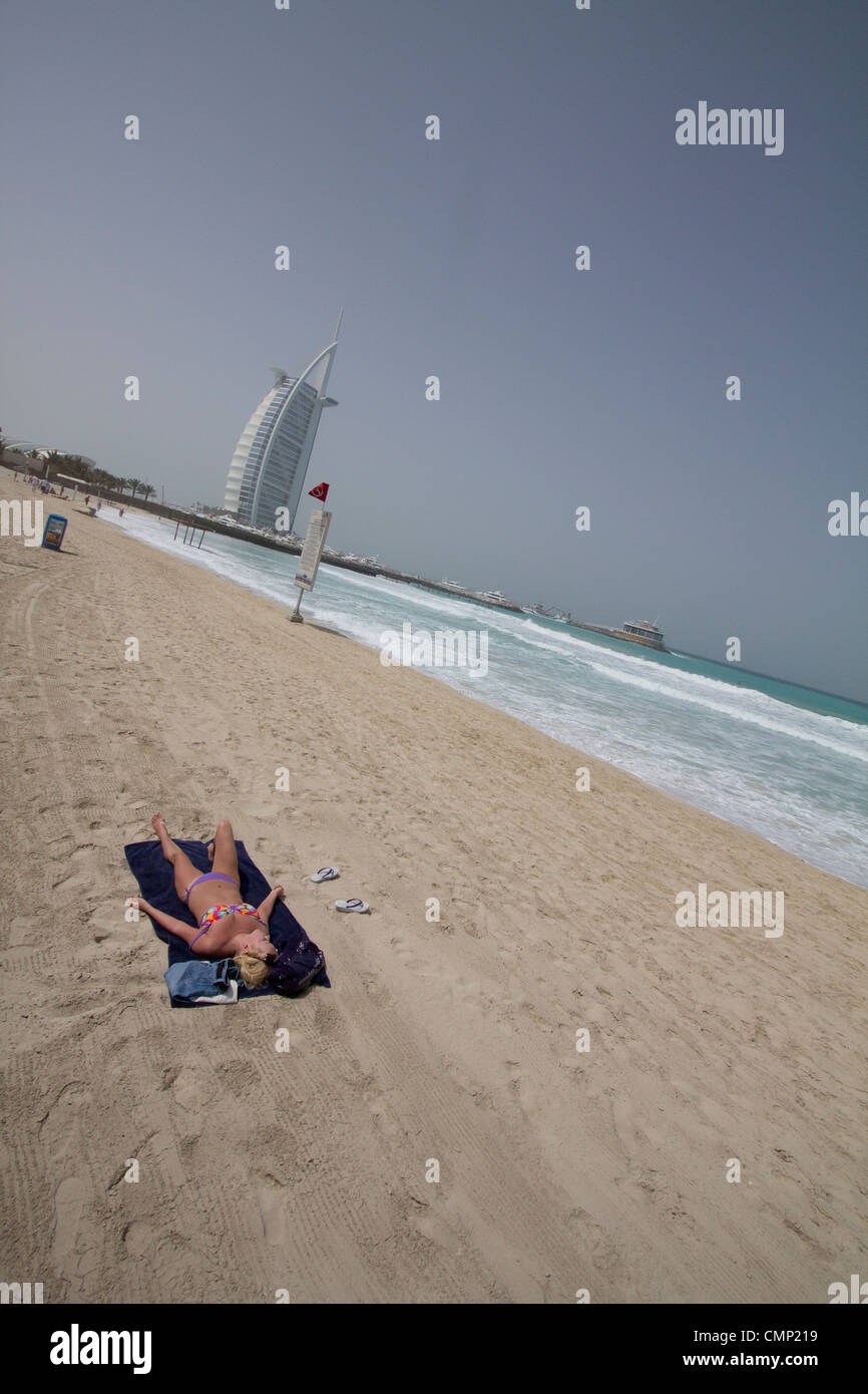 united arab emirates, dubai tourist holidaymaker sunbathing by the Burj Al Arab Tower of the Arabs - Stock Image