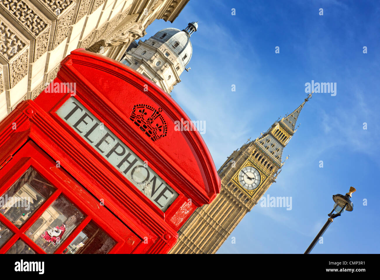 A bright red telephone box at an angle in front or Parliament in Westminster - Stock Image