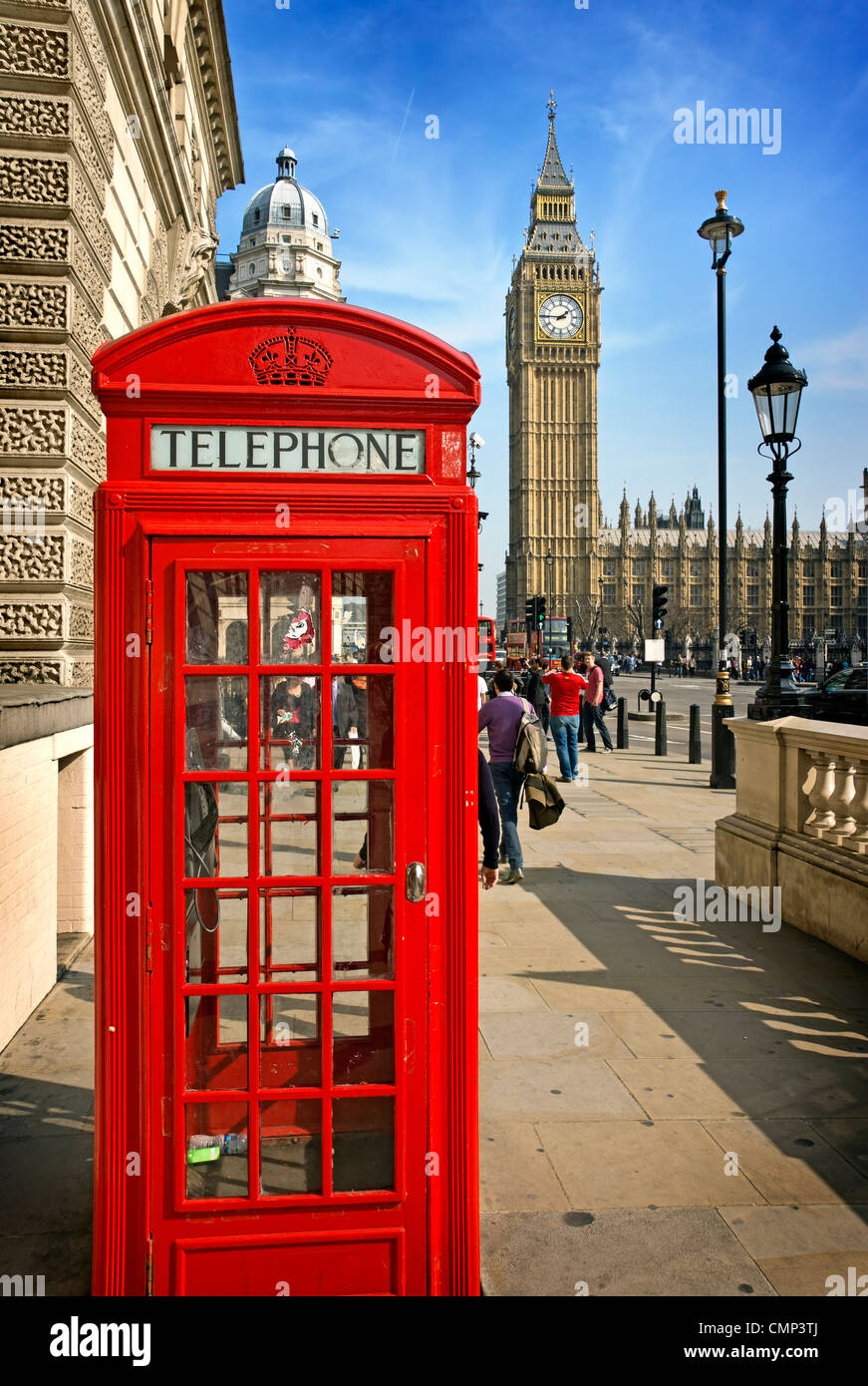 A bright red telephone box in front or Parliament in Westminster - Stock Image