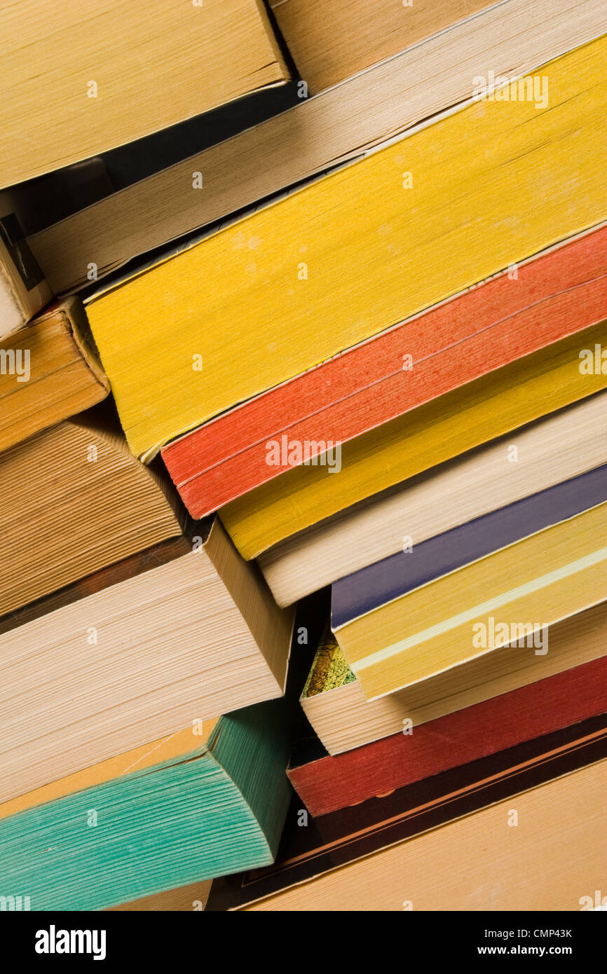 Close-up of pile of old, worn paperback books stacked. Angled view. Page spines facing viewer. Various color pages. - Stock Image