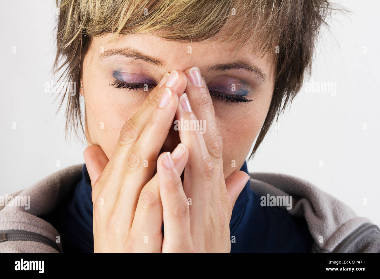 Exhausted young woman holding her hands in front of her her face - female portrait with closed eyes. Studio shot Stock Photo