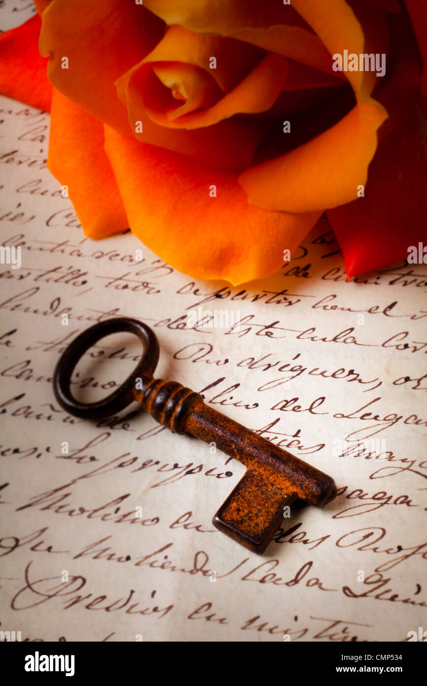 Old skeleton key on hand written letter with orange rose - Stock Image