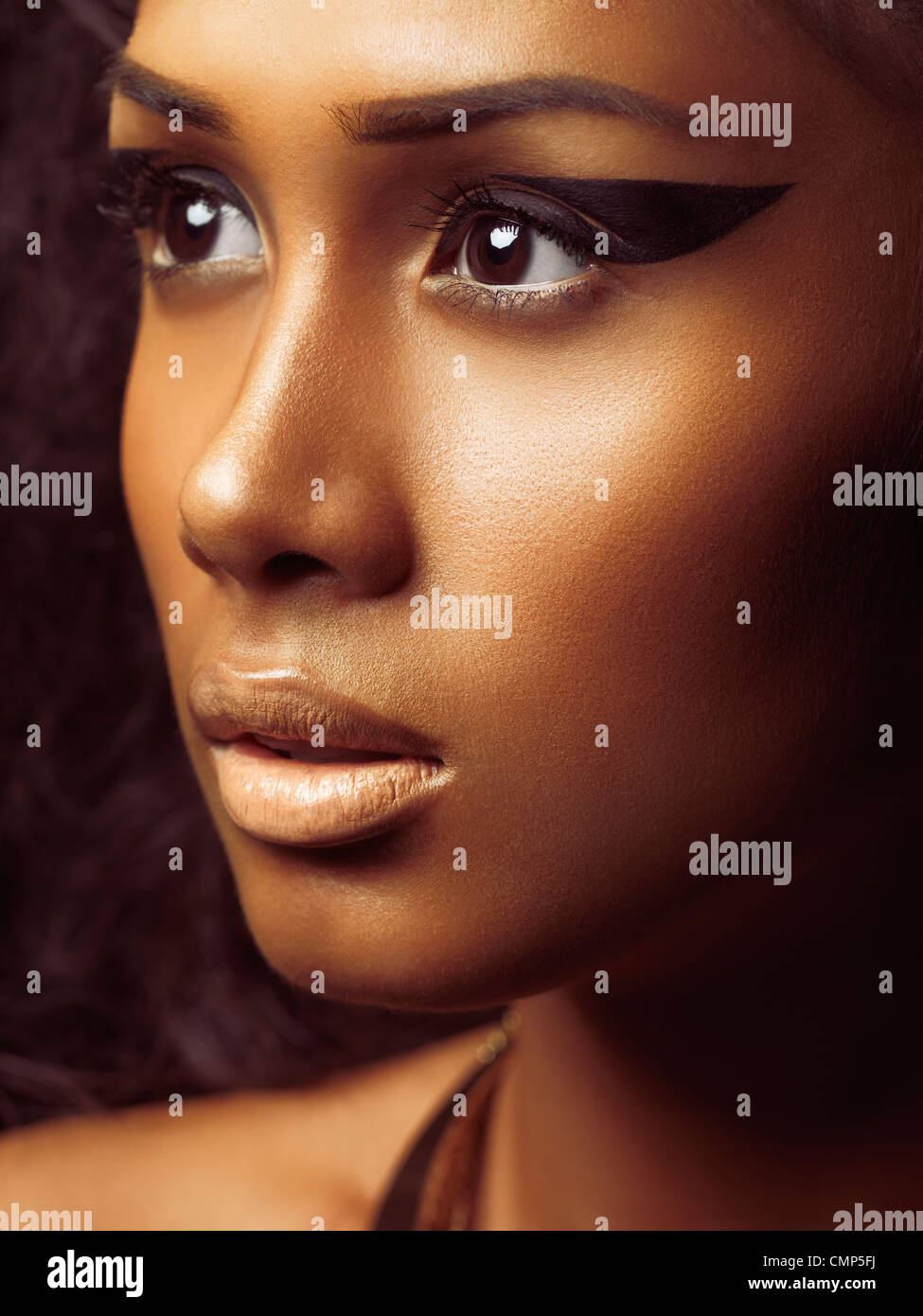Exotic closeup beauty portrait of a young beautiful woman's face with golden skin and artistic makeup - Stock Image