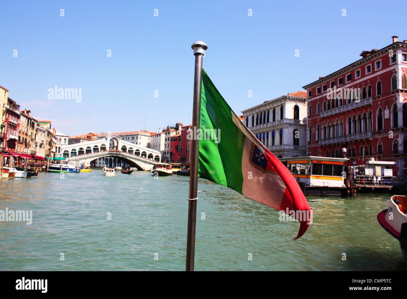 Rialto bridge and flag Venice, Italy Stock Photo