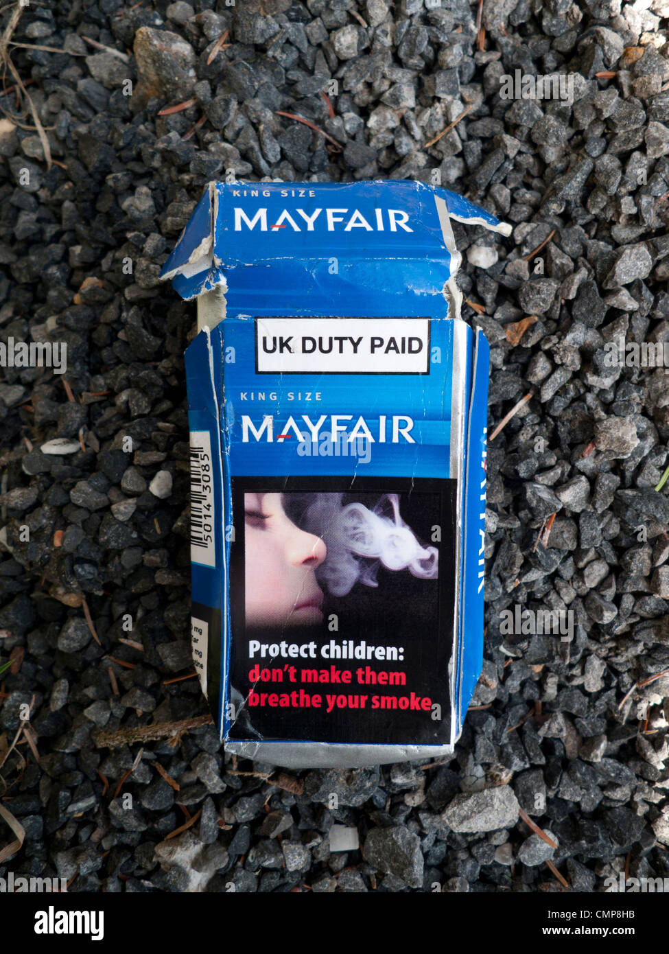A discarded cigarette packet cigarettes depicting a child breathing smoke and a passive smoking danger to health - Stock Image