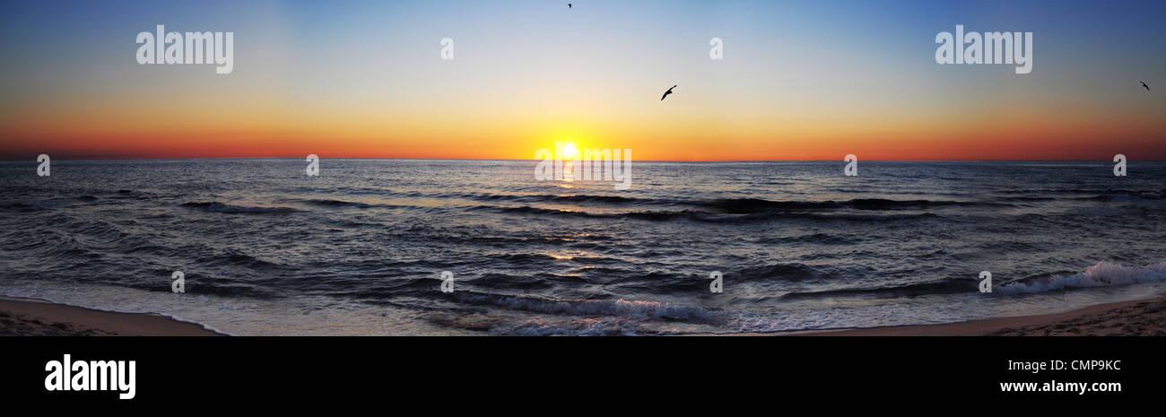 Panorama shot of sun rising over the sea - Stock Image