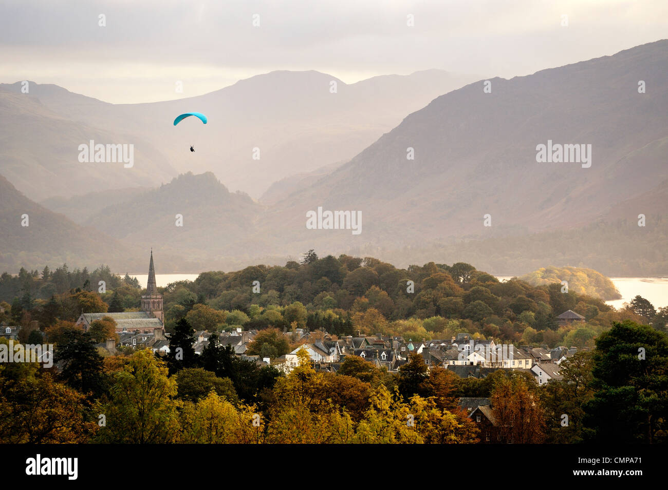 Lake District National Park, Cumbria, England. Paraglider over Keswick town and Derwentwater. South toward Borrowdale. - Stock Image