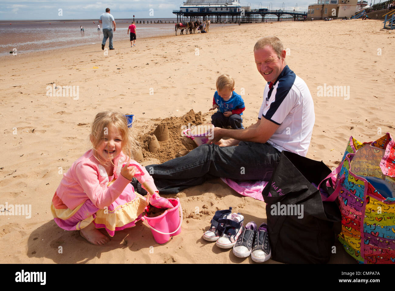 UK, England, Lincolnshire, Cleethorpes, family making sandcastles on beach in sunshine beside the pier - Stock Image