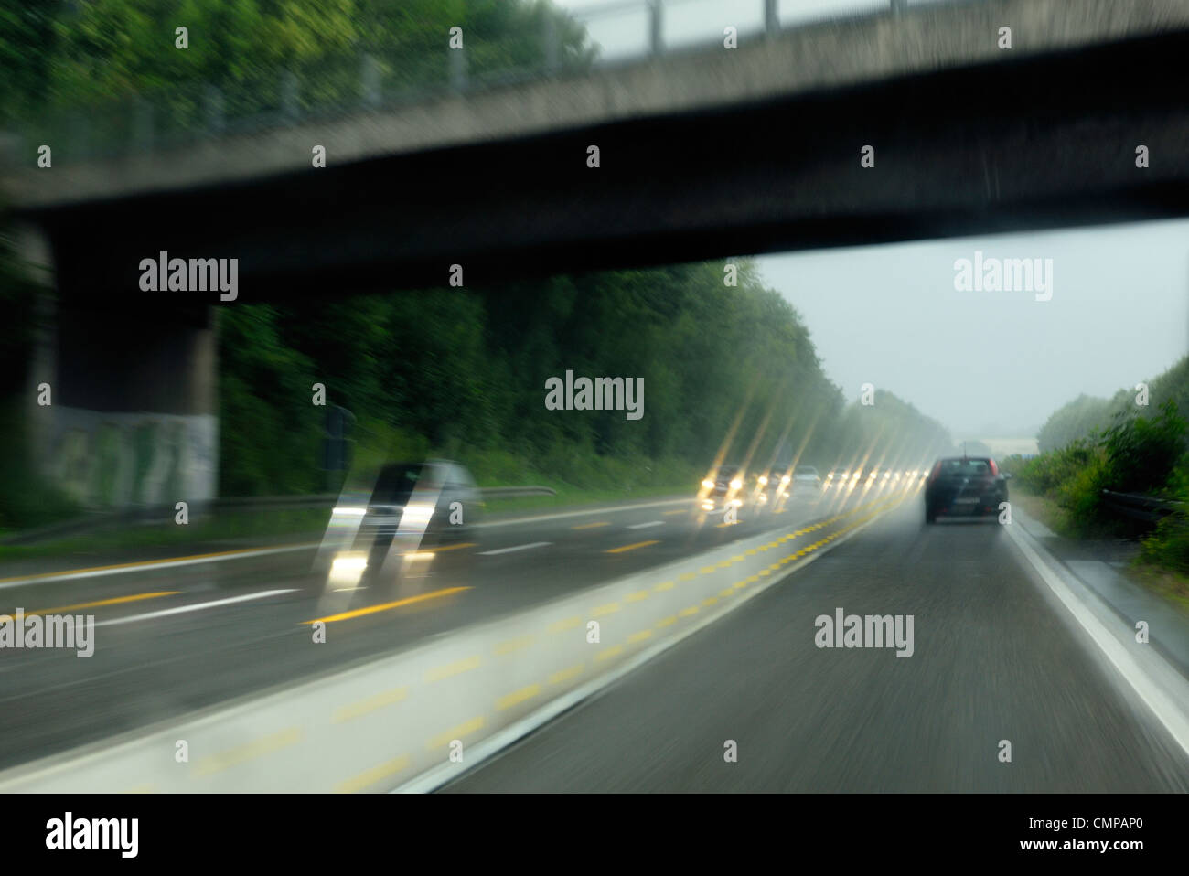 Deliberate motion blur. Driving on German autobahn motorway in Nordrhein-Westfalen near Dusseldorf and Essen on - Stock Image