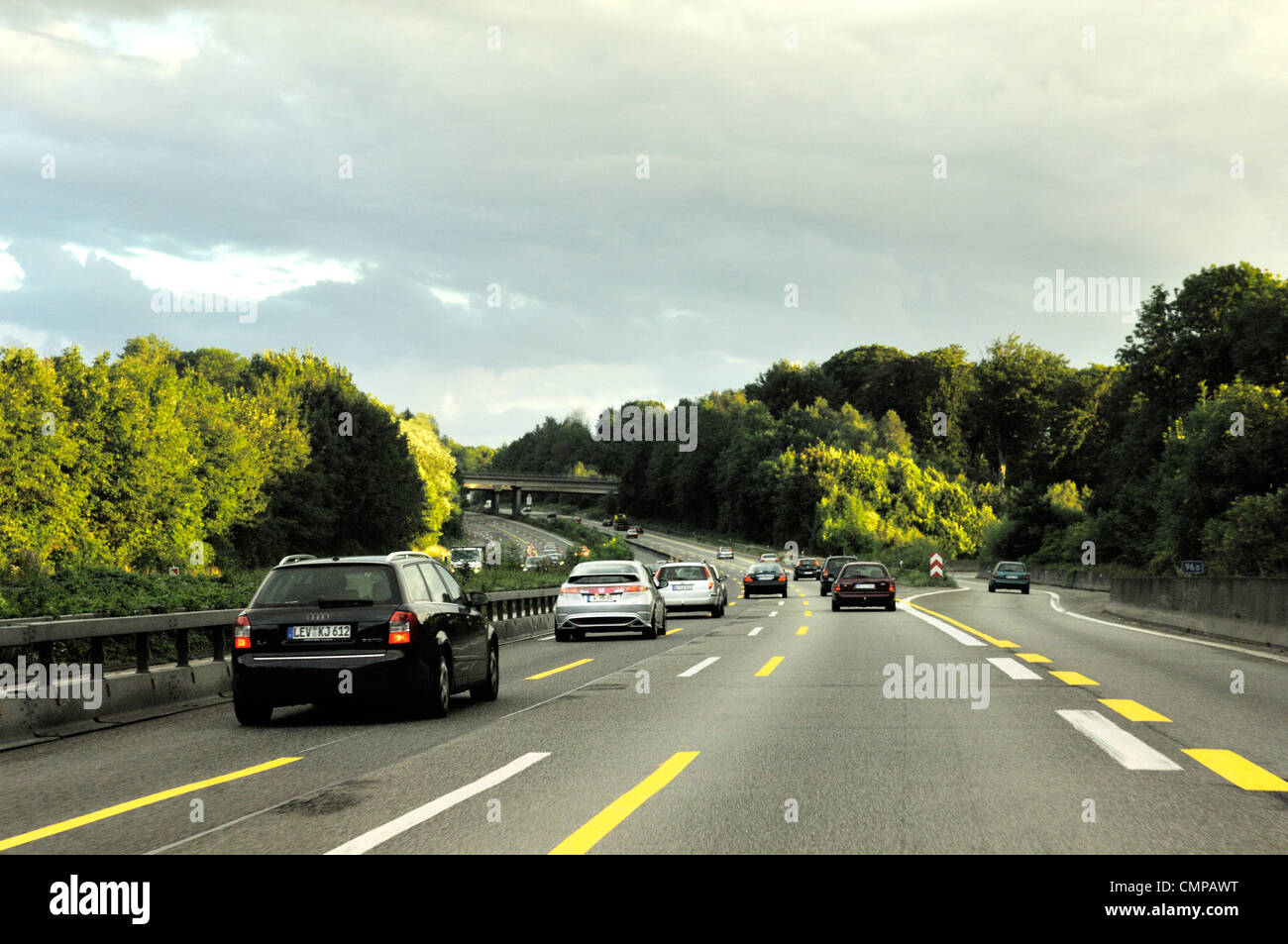 Driving on German autobahn motorway in Nordrhein-Westfalen. Turn off intersection near Dusseldorf. Evening light - Stock Image