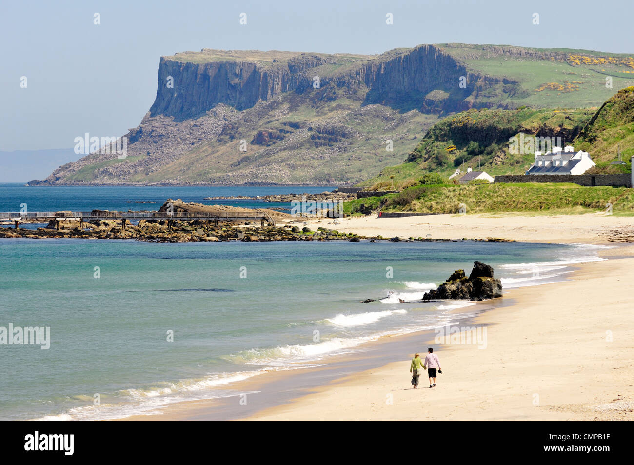Young couple walking on Ballycastle Beach, County Antrim, Northern Ireland. Looking toward the headland of Fair - Stock Image
