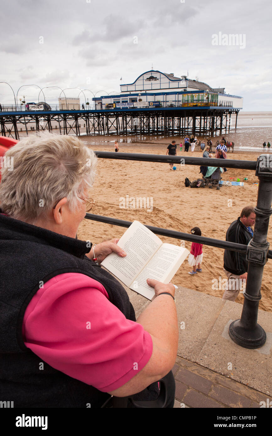 UK, England, Lincolnshire, Cleethorpes, visitor reading book on seafront beside the pier - Stock Image